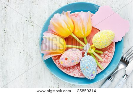 Easter table setting with flowers, empty greeting card and easter egg, beautiful Easter food composition top view blank space for text