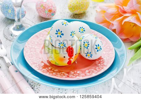 Easter place setting with floral easter eggs and stand for egg in the form of chicken festive Easter composition selective focus