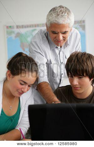 Retrato de um menino e uma menina na frente de um computador portátil em uma sala de aula