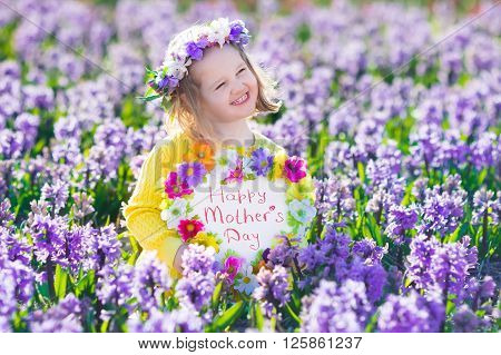 Child playing in hyacinth field. Little girl holding a wooden heart shape chalk board standing in a park with spring hyacinths flowers. Copy space for your text. Happy mother's day card.