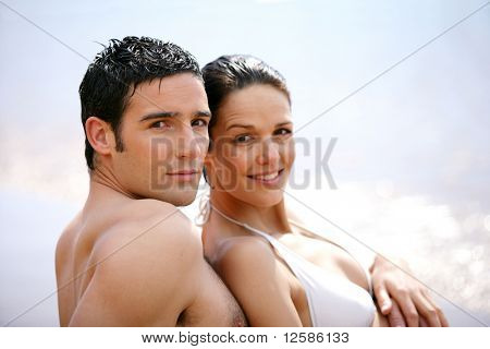 Portrait of a young couple in swimsuit sitting on the sand