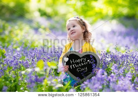 Child playing in bluebells forest. Little girl holding a wooden heart shape chalk board standing in a park with beautiful spring bluebell flowers. Copy space for your text. Kids having fun outdoors in spring.
