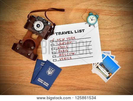 Camera passport and paper with drawing travel list. Work desk tourist.