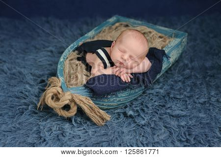 Portrait of a two week old newborn baby boy. He is sleeping in a miniature boat and wearing dark blue overalls. Shot in the studio on a blue flokati rug.