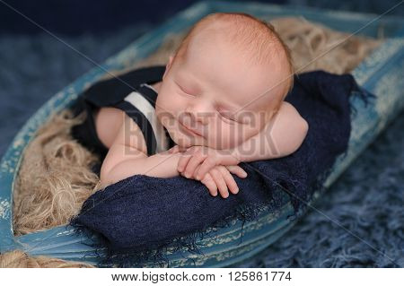 Portrait of a smiling two week old newborn baby boy. He is sleeping in a miniature boat and wearing dark blue overalls. Shot in the studio on a blue flokati rug.