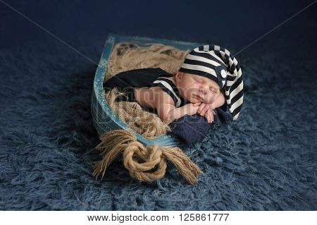 Portrait of a two week old newborn baby boy. He is sleeping in a miniature boat and wearing a dark blue and white striped hat and overalls. Shot in the studio on a blue flokati rug.