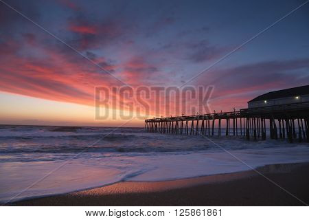 The rising sun visible through pier supports and is reflected in waves by the Nags Head fishing pier on the outer banks of North Carolina