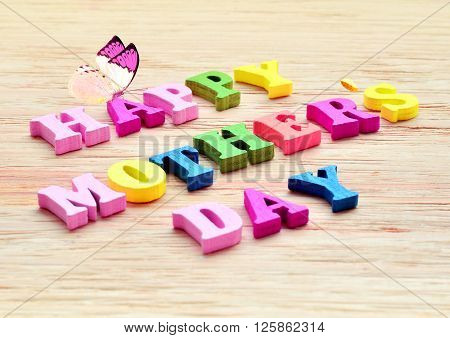 Happy Mothers Day colorful letters spelling greeting on rustic wood table with butterfly