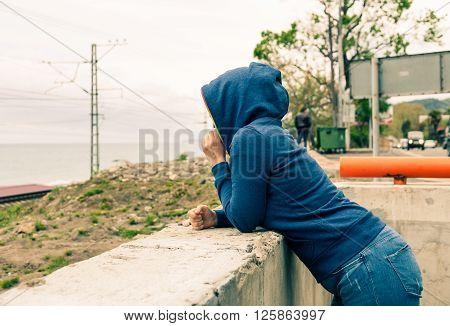 Women in hoody looking at horizon over water