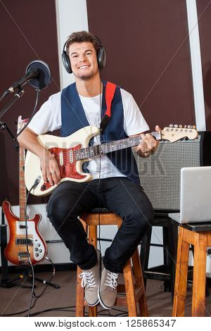 Confident Man Playing Guitar While Sitting On Stool