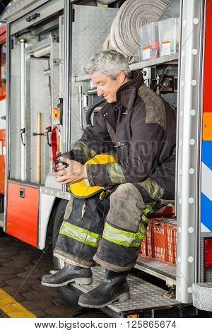 Smiling Fireman Looking At Coffee Mug While In Truck
