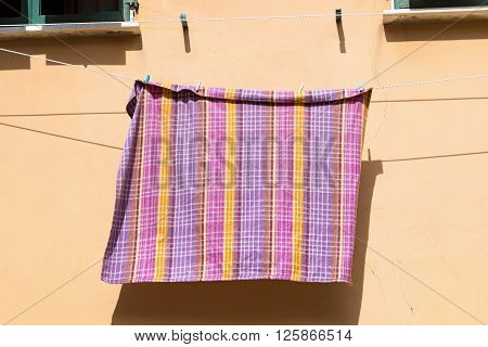 Checkered tablecloth hanging out the window to dry in Portovenere. Liguria La Spezia - Italy