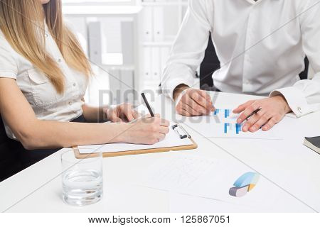 Businesspeople discussing business report at office desk