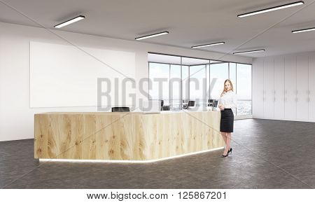 Businesswoman at empty reception with laptops big white board on wall behind. Concept of reception.