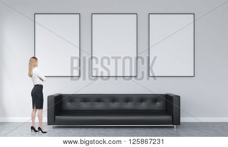 Three white picture frames above black sofa in concrete interior with businesswoman lookign at them. Mock up 3D Rendering