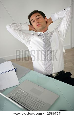 Portrait of a young man stretching in front of a laptop computer