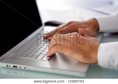 Hands of a man typing on a keyboard of  a laptop computer