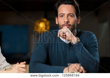 Portrait of a young man with hand on chin looking at camera. Young businessman thinking about plan. Business man working at office until late.