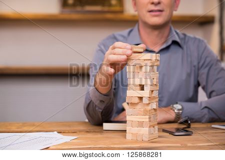 Businessman thinking of expansion with the help of building wooden bricks. Leader gambling placing wooden block on a tower. Business man trying to find a solution to problem with wooden bricks.