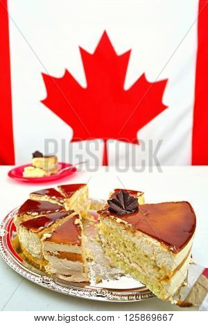 A slice of Maple Mousse Cake for Canada Day celebrations on July 1st. The focus is on the chocolate maple leaf. The Canadian Flag is blurred in the background providing copy space.