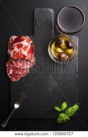 Glass of red wine, meat appetizer, olives and basil on black  slate stone board over dark background. Top view, copy space