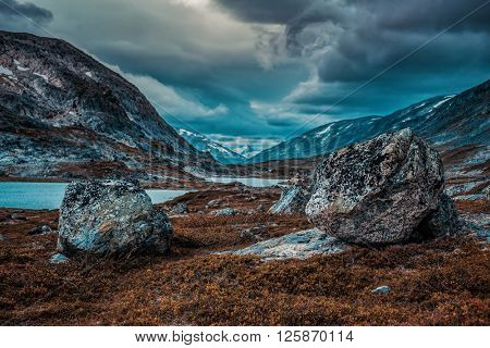 Norway high mountains landscape with small lake. Autumn film style dramatic colors.