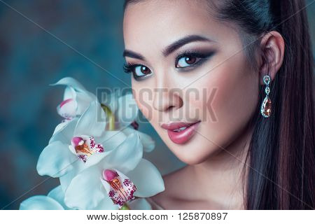 Young asian woman with orchid flower portrait