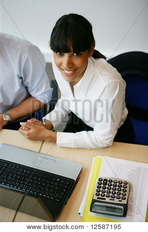 Portrait of a young woman smiling sitting at a desk in front of a laptop computer