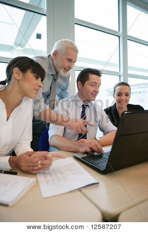 Smiling business people sitting at a desk in front of a laptop computer