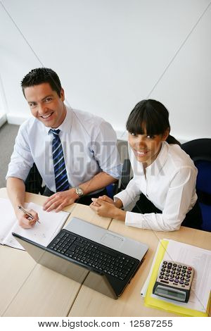 Portrait of a young man and a young woman smiling in front of a laptop computer