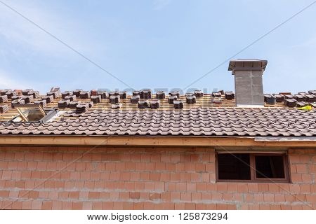 A roof with chimney under construction with stacks of roof tiles ready to fasten