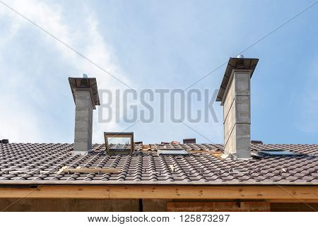 House under construction. Roofing tiles installation. New roof with skylight and chimneys