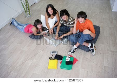 Group of teenagers listening to music near a boy sitting in front of a laptop computer
