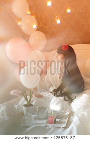 Girl has breakfast in bed. Birthday. Girl drinks coffee with a cake. Good morning. Warm toning. Double Exposure.
