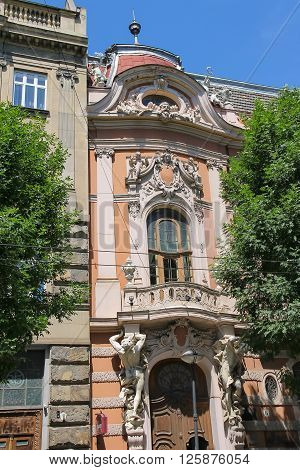 Lviv Ukraine - July 5 2014: Old house with angels on roof and atlas on both sides of the entrance in historical city center (Lystopadovoho Chynu St)