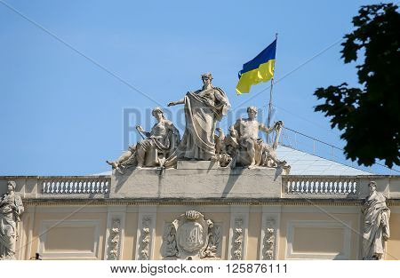 The upper part of Ivan Franko National University main building with National Flag of Ukraine. Allegorical sculpture composition Galicia Vistula and Dniester. Lviv Ukraine