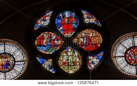 TOLEDO, SPAIN -  MAY 16, 2014 Jesus Mary God the Father Stained Glass Cathedral Spanish Flag Toledo Spain. Cathedral started in 1226 finished 1493