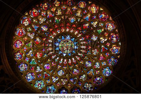 TOLEDO, SPAIN -  MAY 16, 2014 Rose Window Coat Arms Cardinal Hat Stained Glass Cathedral Spanish Flag Toledo Spain. Cathedral started in 1226 finished 1493