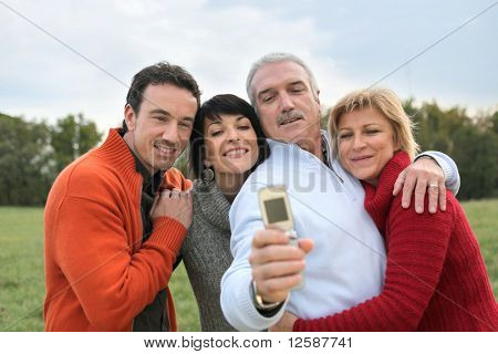 Portrait of smiling men and women in the countryside taking a photo with a mobile phone
