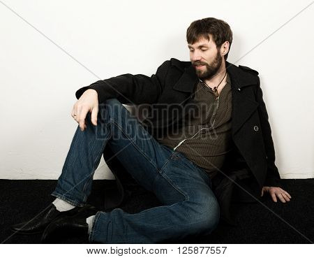 Handsome bearded elegant business man in a jacket, jeans and a woolen coat posing. feshion concept.
