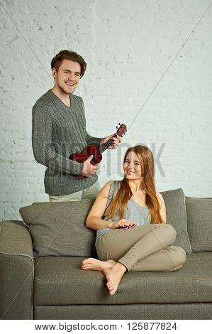 Young man playing ukulele to his smiling girlfriend in living room