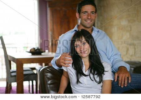 Young couple smiling sitting in an armchair