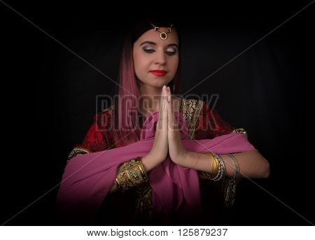 Closeup of Beautiful caucasian woman dressed in oriental style with oriental patterns on the hands and face, with numerous bracelets. Indian woman doing namaste hands sign.