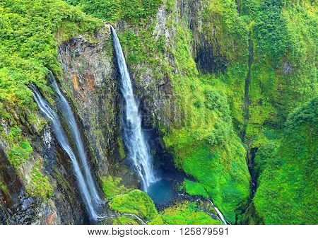 Aerial view to waterfall in tropical rainforest. Cirque Salazie is amazing scenery in center Reunion Island, overseas department of France.