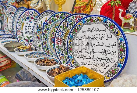 The colorful plates with floral ptterns wishes good luck Surahs from Quran are the traditional souvenirs in Arab market Jerusalem Israel.