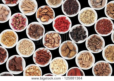 Chinese herb selection used in traditional alternative herbal medicine in porcelain bowls over black background.