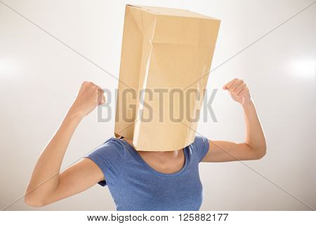 Woman with paper bag cover her head and showing her muscle