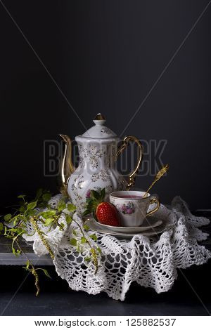 Still life of tea in a porcelain bowl with strawberries on a dark background