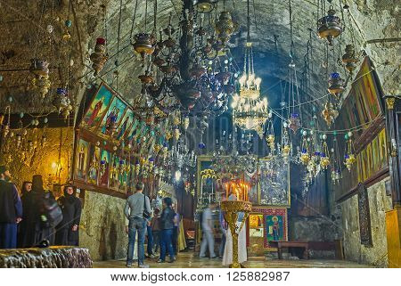JERUSALEM ISRAEL - FEBRUARY 16 2016: The dark prayer hall of the underground Church of the Assumption (Mary's Tomb) decorated with the numerous chandeliers and oil lamps on February 16 in Jerusalem