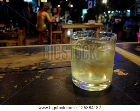Glass of whiskey and ice cubes on wooden table with nightlife background.